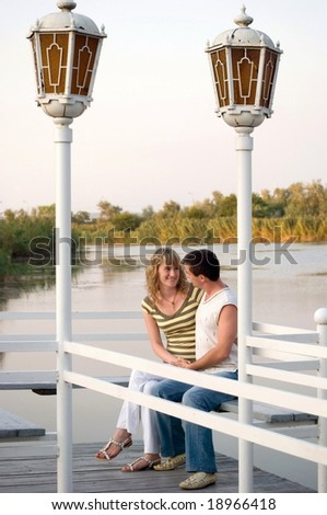 Pair on a pier. Look against each other and smile - stock photo