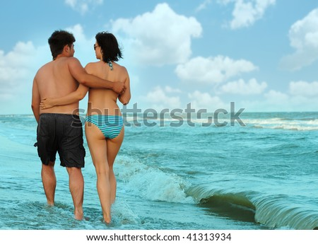 Pair on seacoast. The enamoured guy and the girl walking on coast - stock photo