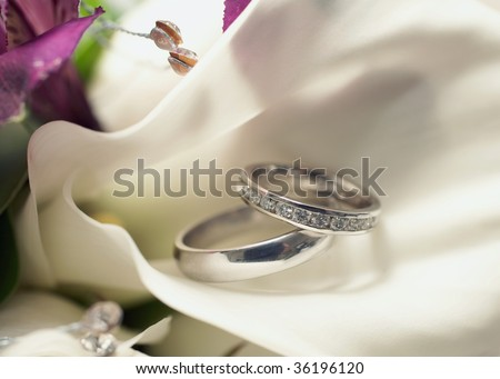 Pair or wedding rings on bouquet flower, focus on diamonds