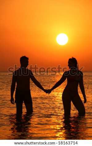 Pair silhouette keeps for hands in sea on sunset