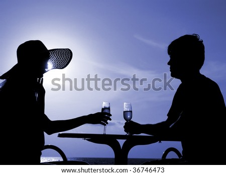 Pair silhouette sit at a table and hold goblet with wine on a moon night