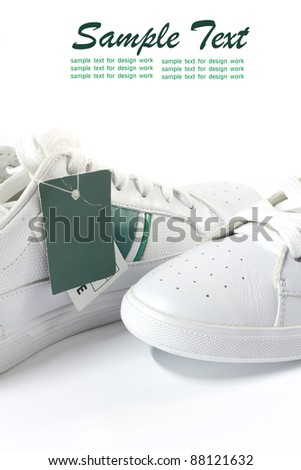 Pair white of sport shoes and Blank Green paper price tag. closeup Useful as background for design-works. - stock photo
