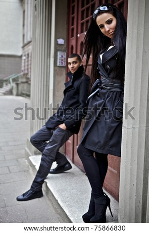 Pair young people near an input in an old building. Evening outdoor shoot. - stock photo