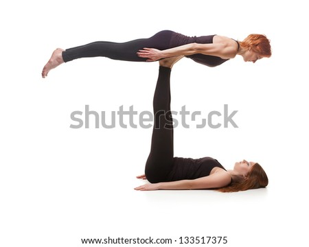 paired yoga. Two women practicing yoga on a white background - stock photo