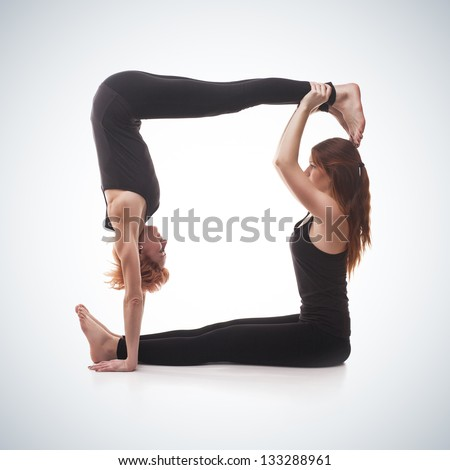 paired yoga. Two women practicing yoga on blue gradient background - stock photo