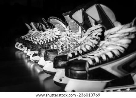 Pairs of hockey skates lined up in a locker room - stock photo