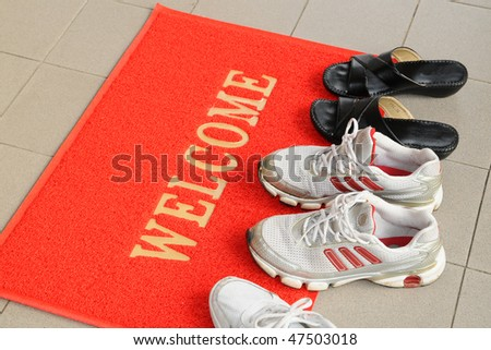 Pairs Of Shoes On A Welcome Mat - stock photo
