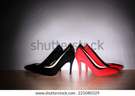 Pairs of woman's red and black shoes on floor on light wall background - stock photo