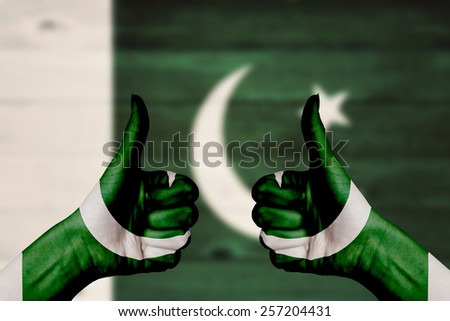 Pakistan flag painted on female hands thumbs up with blurry wooden background - stock photo
