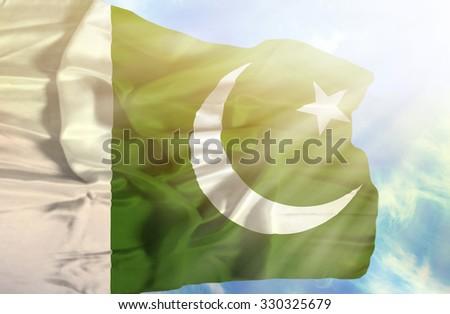 Pakistan waving flag against blue sky with sunrays - stock photo