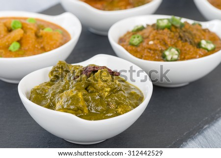 Palak Paneer - Cottage cheese cooked in a pureed spinach curry sauce. Other vegetarian curries on background. - stock photo