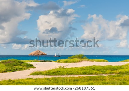 Palapa in deserted beach and turquoise blue caribbean sea - Aruba - stock photo
