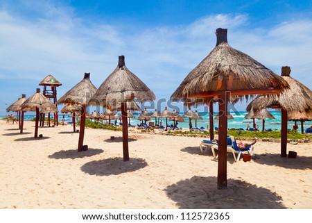 Palapa sun roof beach umbrellas in Caribbean Sea, Mayan Riviera, Mexico - stock photo