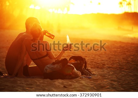 PALAWAN/PHILIPPINES - CIRCA DECEMBER 2015: Truelove couple  with bottles of drink under an orange sunset in Nacpan beach