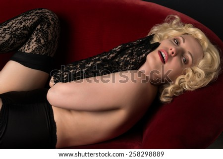 Pale blonde on a red couch topless in black - stock photo