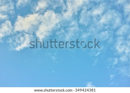 Pale blue sky saturated color. White scattered clouds. - stock photo