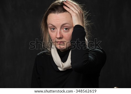 pale confused woman touching her head on gray background