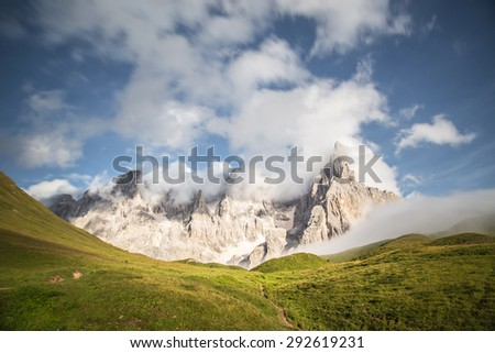 Pale di San Martino, Trentino Alto Adige, Italy. The Pale group standing over a green grass field in a cloudy and windy day with blue sky. - stock photo