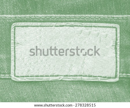 pale green leather label on green jeans background  - stock photo