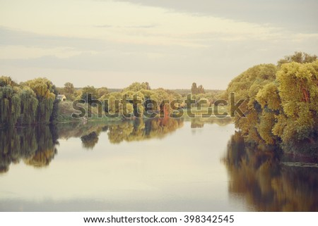pale landscape river trees in water with reflection European - stock photo