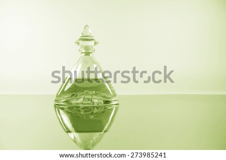 pale lime perfume on the mirror surface - stock photo