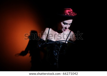 Pale looking woman dressed in black with whip - stock photo