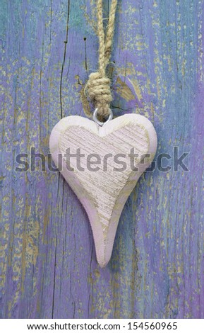 Pale pink wooden heart shape on purple wooden surface. - stock photo