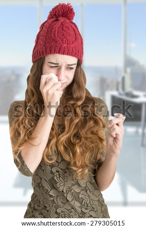Pale sick woman with a flu checking if she has a fever with a thermometer in an office - stock photo