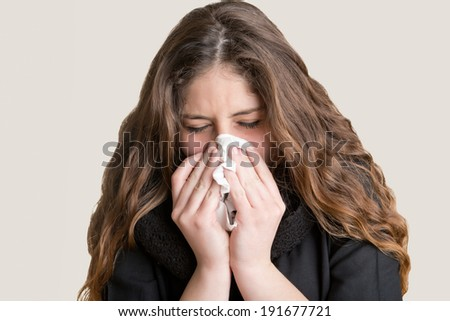 Pale sick woman with a flu, sneezing, in a clean background - stock photo
