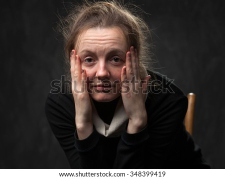 pale tired woman looking straight, touching her face with arms