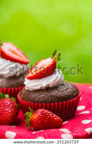 Paleo chocolate and coconut cream cupcakes with strawberries - stock photo