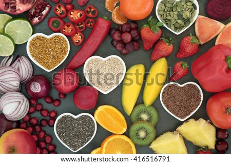 Paleo diet health and super food of fruit, vegetables, nuts and seeds in heart shaped bowls on slate background, high in vitamins, anthocyanins, antioxidants, dietary fiber and minerals. - stock photo