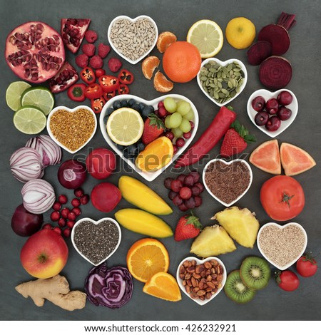 Paleolithic diet health and superfood of fruit, vegetables, nuts and seeds in heart shaped bowls on slate background, high in vitamins, antioxidants, anthocyanins, dietary fiber and minerals. - stock photo