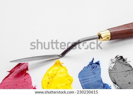 palette knife closeup and oil paints on white artist canvas - stock photo