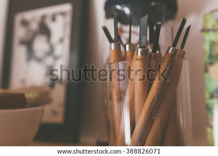 Palette knifes with wooden handles standing in transparent glass. Toned. - stock photo