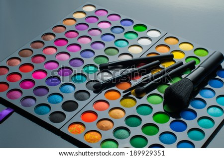 Palette of colorful eye shadows with professional brushes