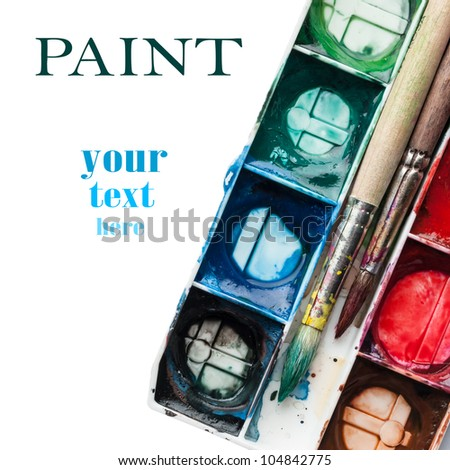 Palette of watercolor paints with paintbrushes and space for your text. - stock photo