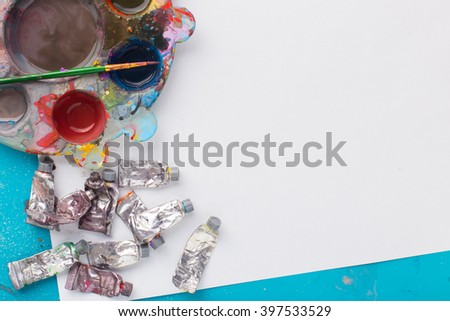 palette paint and paintbrush with white paper on blue table  - stock photo
