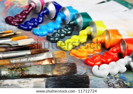 Palette with oil paint and brushes, focus on foreground brushes - stock photo