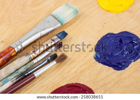 Palette with oil paint and brushes, on the wooden background. - stock photo