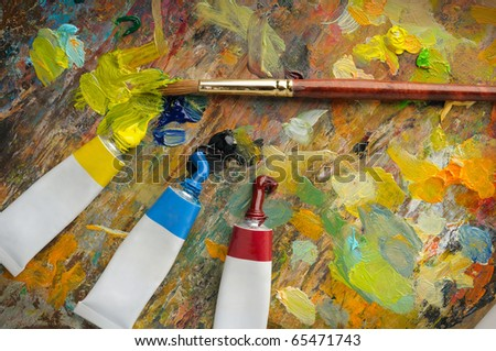 Palette with paint brush and tubes of oil paint - stock photo