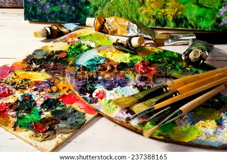 palette with paintbrushes and canvas  paintings - stock photo