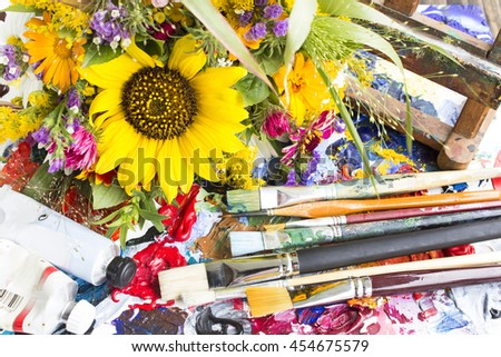 Palette with Painting Material and a Bouquet of Summer Flowers . - stock photo