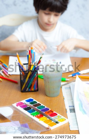 palette with paints, colored pencils in a glass and a young artist - stock photo
