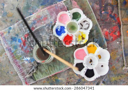 palettes and paintbrush on table paint - stock photo