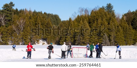 PALGRAVE, ONTARIO - MARCH 8: Boys playing a game of ice hockey on an outdoor skating rink in Palgrave village in Ontario on March 8, 2015.   - stock photo