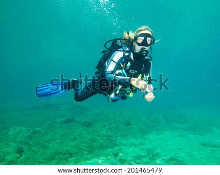 PALIOURI,GREECE-JUNE 27 2014: A female scuba diver taking part in a dive in the Agean Sea of the coast of Halkidiki Greece. Diving is an adventurous sport with diving locations all over the world. - stock photo