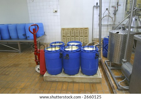 pallet truck with raw processed cheese in dairy with production system in background - stock photo