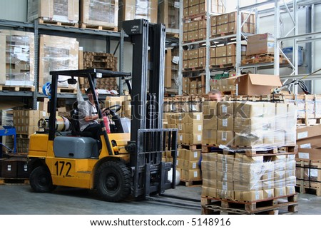 Pallet truck working at the warehouse - stock photo