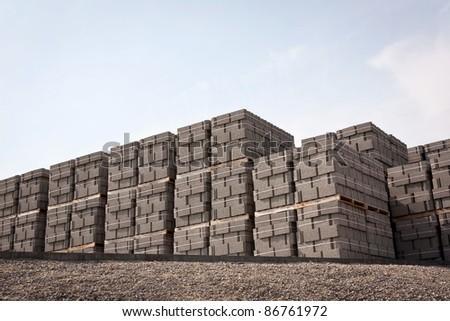 pallets of new concrete blocks under sunlight against blue sky - stock photo